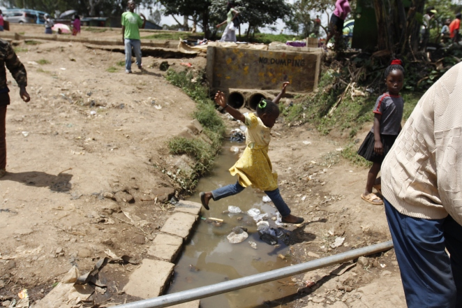 A girl jumps across a raw sewerage in Nairobi's Kibera slums