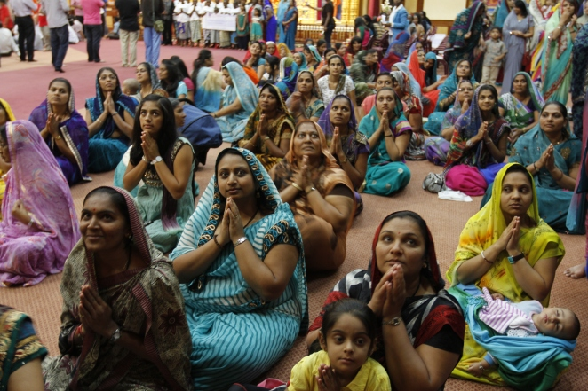 A group of Hindu women watch as his holiness Acharya Purshottam Priyadasji Swamishree Maharaj leave Shree Swaminaryan Gadi Temple Parklands Nairobi after a ceremony
